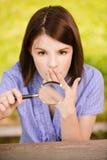 Ritratto di giovane donna con la lente di ingrandimento Immagini Stock Libere da Diritti