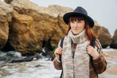 Ritratto di giovane donna dai capelli rossi in un cappello ed in una sciarpa con uno zaino contro lo sfondo delle rocce contro fotografia stock libera da diritti