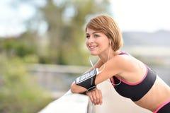 Ritratto di giovane donna del pareggiatore con lo smartphone sul suo braccio Immagini Stock