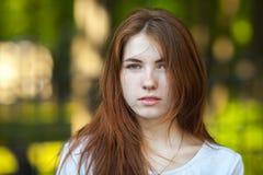 Ritratto di giovane donna della testarossa che fissa nei precedenti confusi all'aperto di Forest Park della macchina fotografica Fotografie Stock Libere da Diritti