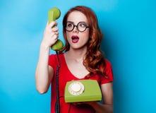 Ritratto di giovane donna della testarossa con il microtelefono immagine stock