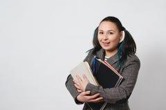 Ritratto di giovane donna dello studente che tiene i libri e le cartelle immagine stock libera da diritti