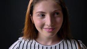 Ritratto di giovane donna dello zenzero che esamina macchina fotografica e che sorride, isolato su fondo nero video d archivio