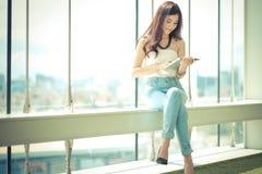 Ritratto di giovane donna di affari casuale che per mezzo della compressa Fotografia Stock