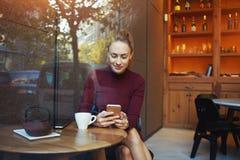 Ritratto di giovane donna di affari che per mezzo del telefono cellulare mentre sedendosi nell'interno comodo della caffetteria, Immagini Stock Libere da Diritti