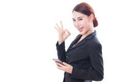 Ritratto di giovane donna di affari che per mezzo di un telefono cellulare e mostrando segno giusto fotografia stock