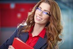 Ritratto di giovane donna di affari che sorride, in un'en dell'ufficio Fotografie Stock Libere da Diritti