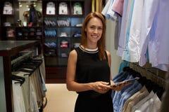 Ritratto di giovane donna di affari con il bello sorriso che tiene compressa digitale mentre stando nel suo boutique di modo Immagine Stock Libera da Diritti