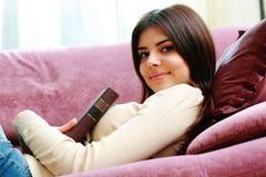 Ritratto di giovane donna felice che si trova sul sofà con il libro Fotografia Stock Libera da Diritti