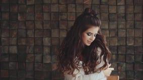 Ritratto di giovane donna graziosa con trucco luminoso che posa, esaminante la macchina fotografica archivi video