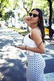 Ritratto di giovane donna latina con la figura perfetta facendo uso del telefono delle cellule mentre stando sulla via nel giorno Immagini Stock