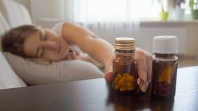 Ritratto di giovane donna malata che si trova sul letto e che prende bottiglia con le pillole dal comodino Immagine Stock Libera da Diritti
