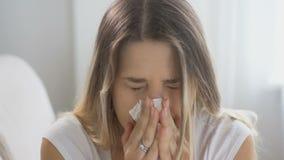 Ritratto di giovane donna malata che starnutisce in fazzoletto Metraggio sparato in 4K stock footage
