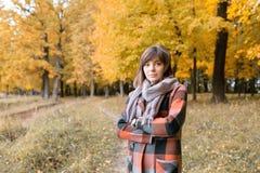 Ritratto di giovane donna di modo all'aperto Donna castana nel parco di autunno con il cappotto e la sciarpa alla moda del plaid fotografie stock