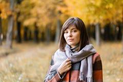Ritratto di giovane donna di modo all'aperto Donna castana nel parco di autunno con il cappotto e la sciarpa alla moda del plaid immagini stock libere da diritti