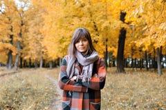 Ritratto di giovane donna di modo all'aperto Donna castana nel parco di autunno con il cappotto e la sciarpa alla moda del plaid fotografie stock libere da diritti