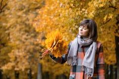 Ritratto di giovane donna di modo all'aperto Donna castana nel parco di autunno con il cappotto e la sciarpa alla moda del plaid  fotografia stock