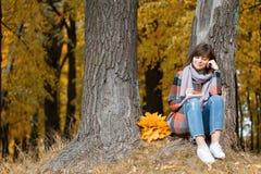 Ritratto di giovane donna di modo all'aperto Scrive in un taccuino Donna castana nel parco di autunno con il cappotto alla moda d immagine stock libera da diritti