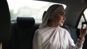 Ritratto di giovane donna musulmana in foulard beige, sedentesi nell'automobile mentre esaminando un piccolo specchio cosmetico e stock footage