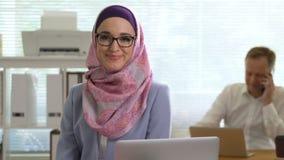 Ritratto di giovane donna musulmana professionale di affari che esamina risata della macchina fotografica video d archivio