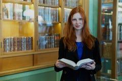 Ritratto di giovane donna redheaded in un cappotto con un libro a disposizione fotografia stock libera da diritti