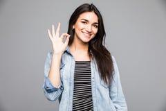 Ritratto di giovane donna sorridente allegra che mostra gesto giusto, con copyspace, sopra grey Immagini Stock