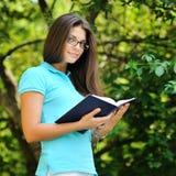 Ritratto di giovane donna sorridente con il libro in un parco verde Immagini Stock Libere da Diritti
