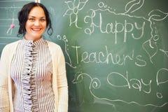 Ritratto di giovane donna sorridente felice dell'insegnante che sta vicino a chal Immagini Stock Libere da Diritti
