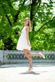 Ritratto di giovane donna sorridente nel salto, all'aperto Immagini Stock