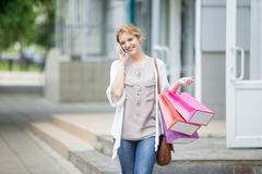 Ritratto di giovane donna sorridente sul telefono cellulare durante l'acquisto Fotografia Stock Libera da Diritti