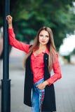 Ritratto di giovane donna sorridente in una camicia rossa ed in un rivestimento senza maniche lungo che esaminano macchina fotogr fotografia stock libera da diritti
