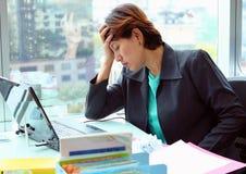 Ritratto di giovane donna stanca di affari con il computer portatile nell'ufficio, donna che tiene la sua testa, concetto di affa Fotografia Stock