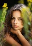 Ritratto di giovane donna sul giacimento di fiori Fotografia Stock Libera da Diritti