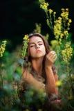 Ritratto di giovane donna sul giacimento di fiori Fotografia Stock