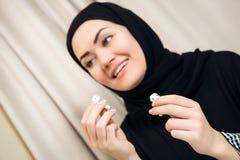 Ritratto di giovane e donna musulmana attraente in un turbante o in un hijab che ascolta il flusso continuo della musica sul suo  immagini stock libere da diritti