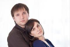 Ritratto di giovane famiglia caucasica che sta abbracciata insieme Immagini Stock