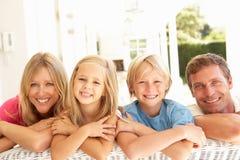 Ritratto di giovane famiglia che si distende insieme sul sofà Fotografie Stock Libere da Diritti