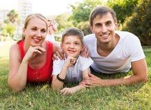 Ritratto di giovane famiglia con il ragazzo che si trova nel parco Fotografie Stock Libere da Diritti