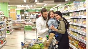 Ritratto di giovane famiglia con la figlia in supermercato, comprano il succo per il bambino archivi video