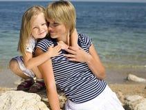 Ritratto di giovane famiglia divertendosi sulla spiaggia, sulla madre e sulla figlia in mare immagine stock