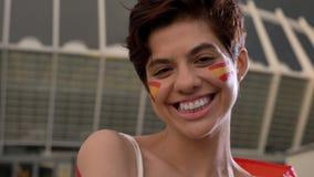 Ritratto di giovane fan di calcio castana della ragazza in Spagna, esaminando la macchina fotografica, sorridendo, ridente, stadi stock footage