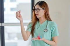 Ritratto di giovane farmacista che mostra le pillole Fotografie Stock