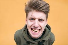 Ritratto di giovane fine dolosa del ragazzo su contro una parete arancio Un giovane arrabbiato e divertente esamina la macchina f fotografie stock