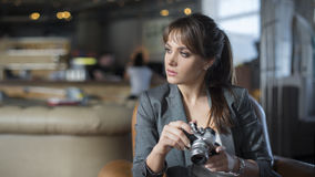 Ritratto di giovane fotografo dell'adolescente con capelli lunghi in maglietta nera in caffè Bella ragazza che tiene vecchia macc Immagine Stock Libera da Diritti