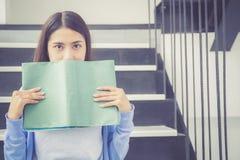 Ritratto di giovane fronte asiatico del pellame della donna di sorriso dietro il libro con svago Immagini Stock Libere da Diritti