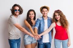 Ritratto di giovane gruppo allegro di amici che un le loro mani in uno studio immagini stock