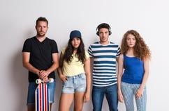 Ritratto di giovane gruppo allegro di amici con il longboard che sta in uno studio fotografie stock libere da diritti