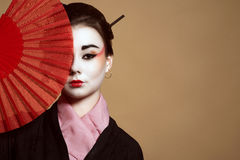 Ritratto di giovane heisha in kimono che nasconde la metà del suo fronte dietro il fan tenuto in mano rosso fotografia stock