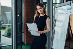 Ritratto di giovane imprenditore femminile che porta vestito convenzionale che tiene il rapporto finanziario che sta nell'ufficio fotografie stock libere da diritti