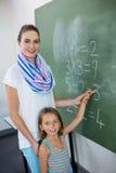 Ritratto di giovane insegnante che assiste scrittura della ragazza sulla lavagna Fotografie Stock